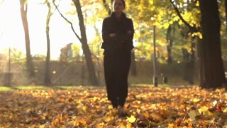 Woman walking on the leaves in the park, slow motion shot
