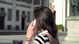 Woman walking on the square and talking on the phone, steadycam shot
