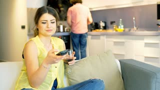 Woman watching television and her boyfriend cooking in the kitchen, steadycam sh