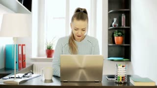 Woman with ponytail working on laptop and texting on smartphone in her office, s