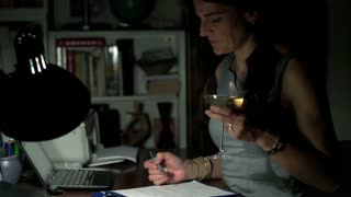 Woman working at night at the desk and holding glass of wine, steadycam shot
