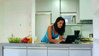 Woman working on laptop in the kitchen and smiling to the camera, steadycam shot