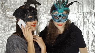 Women chatting on cellphone at the masquerade party, steadycam shot