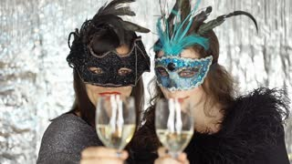 Women drinking champagne and smiling to the camera at the masquerade party, stea