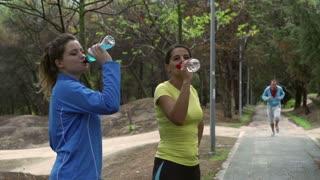 Women drinking liquids after run, slow motion shot at 240fps, steadycam shot