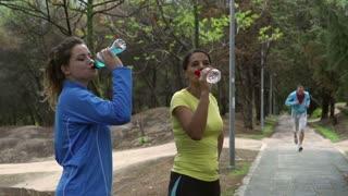 Women drinking liquids after run, slow motion shot, steadycam shot