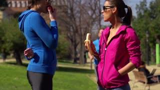 Women eating fruits in park, slow motion shot at 120fps, steadycam shot