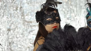 Women in beautiful masks looking serious at the masquerade party, steadycam shot