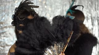 Women in carnival masks meeting at the party and chatting with each other, stead