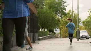Women jogging and man stretching, slow motion shot at 240fps, steadycam shot