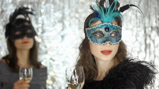 Women looks mysterious in the carnival masks and holding glasses with champagne,