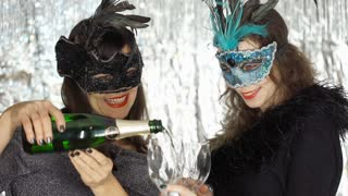 Women pouring champagne to the glasses and enjoying the masquerade party, steady