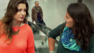 Women riding up by escalator and chatting, steadycam shot
