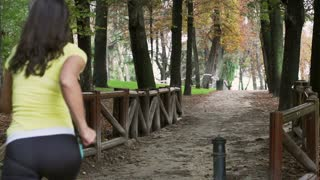 Women running alone in the park, slow motion shot at 240fps, steadycam shot