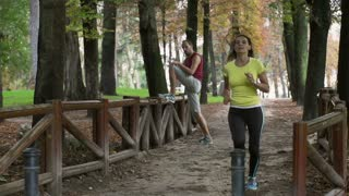 Women running in the park and man stretching legs, slow motion shot at 240fps