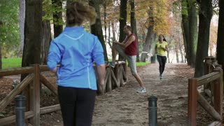 Women running in the park and man warming up, slow motion shot at 240fps, steady