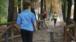 Women running in the park and man warming up, slow motion shot, steadycam shot