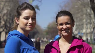 Women smiling to camera in park, slow motion shot at 240fps, steadycam shot
