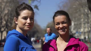 Women smiling to camera in park, slow motion shot at 60fps, steadycam shot