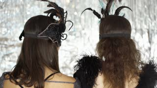 Women turning to the camera and wearing carnival masks, steadycam shot