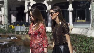 Women walking and talking in park, slow motion shot at 120fps, steadycam shot