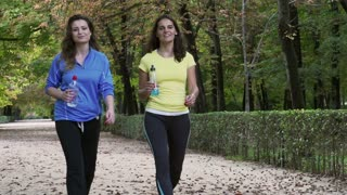 Women walking with liquids in the park, slow motion shot at 240fps, steadycam