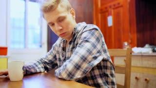 Worried boy sitting in the kitchen and drinking beverage