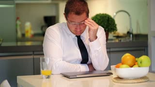Worried businessman sitting at home at the table, steadycam shot