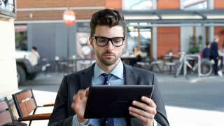 Worried businessman sitting outdoors and browsing internet on tablet, steadycam