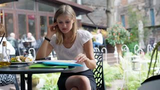 Worried businesswoman looking on papers and having problems