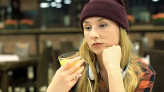 Worried girl sitting in the cafe and drinking orange juice, steadycam shot