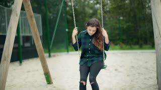 Worried girl sitting on the seesaw and swinging slowly