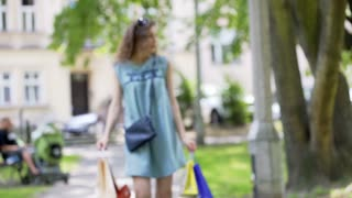 Worried girl walking with shopping bags in the park and having headache