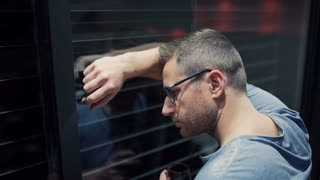 Worried man leaning on window and drinking red wine