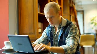 Worried student looking tired while using laptop in the library