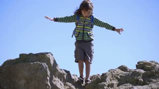Young boy going down from the rock in the seacoast, steadycam shot