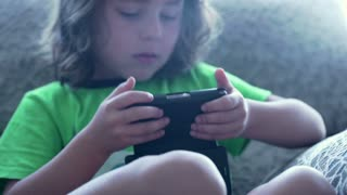 Young boy playing game on smartphone and looking very absorbed, steadycam shot