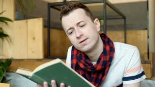Young boy reading book in the cafe and laugh at something