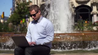 young businessman sitting by fountain with laptop, slow motion shot at 240fps