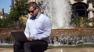 young businessman sitting by fountain with laptop, slow motion shot at 60fps