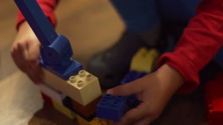 Young child connecting blocks, closeup, slow motion shot at 100fps