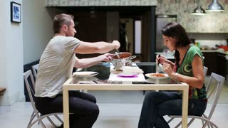Young couple eating dinner at home