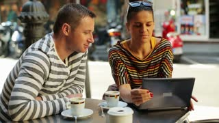 young couple using tablet and sitting by the table outside the cafe