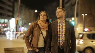 Young couple walking in night city, steadycam shot
