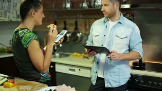 young couple with cellphone and tablet talking and eating in the kitchen