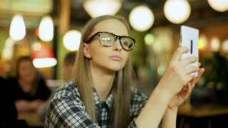 Young girl in plaid shirt doing selfies on smartphone in the cafe