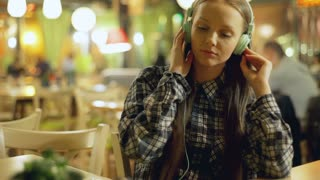 Young girl in plaid shirt listening music in the cafe