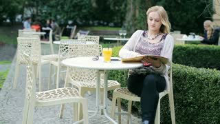 Young girl sitting in the outdoor cafe and reading menu