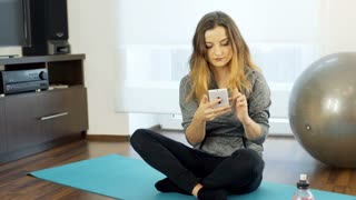 Young girl sitting on the exercising mat and browsing internet on smartphone, st