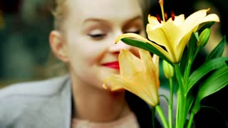 Young girl smelling beautiful flower